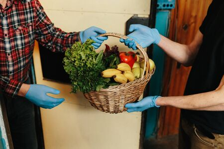 Online shopping concept. Male courier in black uniform, protective mask and gloves with a grocery basket with fresh fruits and vegetables