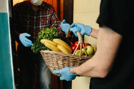 coronavirus pandemic. Epidemic. A volunteer brought food for senior citizens. A volunteer in a medical mask and gloves passes a bag of products to an elderly man in mask. Banque d'images