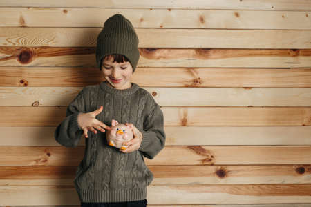 Portrait of cute smiling little boy with piggy bank on wooden background. Child with money in green hat. Stok Fotoğraf