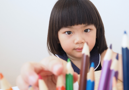 Happy asian kid girl selecting color pencil for drawing picture