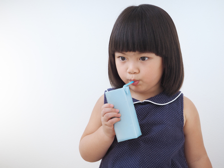 Happy asian kid girl drinking milk from carton box with straw, Blank juice package in hand of healthy child Stock Photo