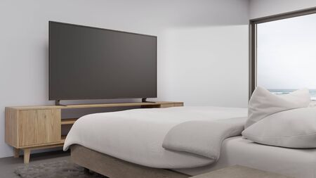 Sea view bedroom of luxury summer beach house with television on TV stand and cabinet near bed. Empty white concrete wall background in vacation home or holiday villa. Hotel interior 3d illustration. 写真素材