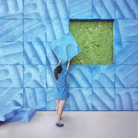 3d rendering of large blue wall on natural green moss. Young woman in denim dress lifting heavy concrete tile.