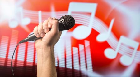 歌、カラオケやボーカル トレーニング コンセプト。抽象的な音楽テーマのメモとイコライザー背景の前に手でマイク。歌のコンテストとのライブ