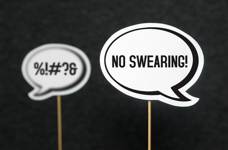 Swearing, cursing and bad language or behaviour in school, work or life. Speech bubble telling the other not to swear. Concept of no dirty words and teaching good manners with speech balloons.