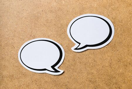 commenting: 2 blank speech bubbles on a light brown wooden cork board background. Chat bubble cut from paper and cardboard. Discussion, chat and commenting concept with a lot of free empty copy space for text. Stock Photo