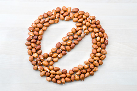 Peanut allergy. Stop, forbidden, prohibited and banned sign and symbol formed with nuts on white wooden table or board. No groundnuts for allergic person. Stock Photo
