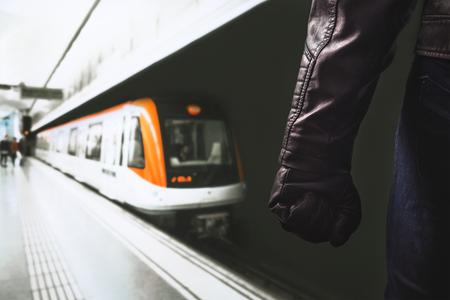公共交通機関での暴力。地下鉄のプラットフォームに立っている危険な男を脅迫します。拳と黒革手袋の腕。怒っている人や地下鉄の犯罪者。窃盗