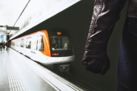 Violence in public transportation. Threatening dangerous man standing in underground subway platform. Fist and arm with black leather glove. Angry person or criminal in metro. Theft and robbery.