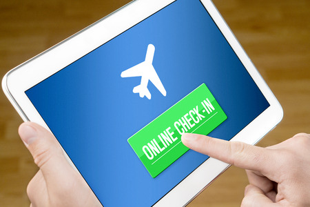 Online check in with mobile device at home. Man checking in to flight with tablet on the web. Internet self service provided by airline. 版權商用圖片