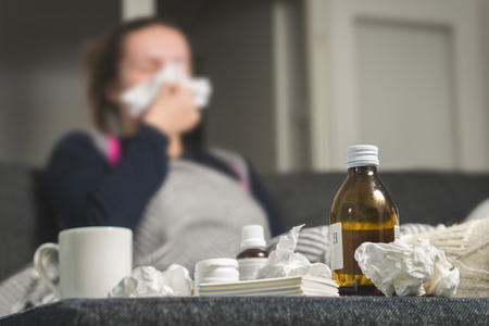 Sick woman sneezing to tissue. Medicine, hot beverage and dirty paper towels in front. Girl caught cold. Cough syrup and handkerchiefs on table. Very ill person feeling bad and having fever. Stock Photo