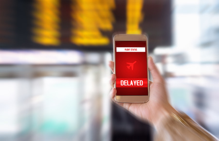Flight delayed. Delay in flying schedule. Aeroplane will take off late. Smartphone application announces bad news to tourist. Woman holding mobile phone in airport terminal. Timetable background. Banque d'images