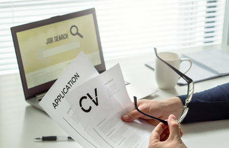 Job seeker in home office. Motivated applicant. Modern job hunting, seeking and employment. Man reading his cv or curriculum vitae and job application paper and trying to find work and get hired. Imagens