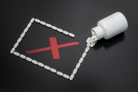 Medicamento incorrecto o negligencia en la medicación. El médico o farmacéutico cometió un error con la prescripción o la droga no funciona. Las píldoras derramadas en la mesa de la botella formando un rectángulo con el signo rojo de la muestra de x dentro. Foto de archivo