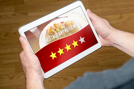 alright: Good restaurant review from satisfied and happy customer and reviewer. Rated four out of five stars. Hands holding tablet with an imaginary criticism application, social media or website on screen.