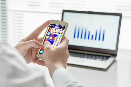 Close-up van luie en onproductieve kantoorwerker die mobiel spel speelt met slimme telefoon tijdens kantooruren. Zijn werk vermijden. Nutteloos en verveeld man doet niets en verliest zijn werk.