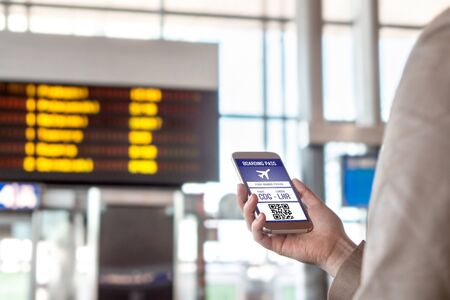 Boarding pass in smartphone. Woman holding phone in airport with mobile ticket on screen. Modern travelling technology and easy access to aeroplane. Terminal and timetable in the blurred background. Stock Photo