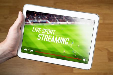 Mens die levende sportstroom online met mobiel apparaat bekijkt. Hand met tablet met denkbeeldige videospeler en streaming-service.