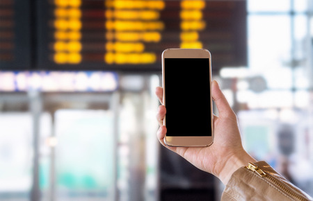 hands free phone: Smartphone with blank screen in bus, train, metro, subway or underground station or airport. Universal public transportation terminal. Hand holding mobile phone with free empty copy space.