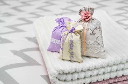 sac: Three lavender scent pouches on towels. Scented sachets on bedroom bed. Fragrance bags for fresh home. Decoration, furnishing and storage accessories. Aromatic potpourri set. Stock Photo