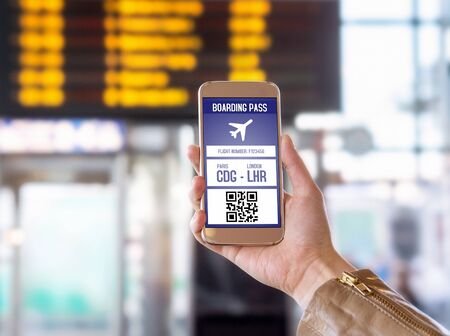Boarding pass in mobile phone. Woman holding smartphone in airport with modern ticket on screen. Easy and fast access to aeroplane. Terminal and timetable in the blurred background. Stock Photo
