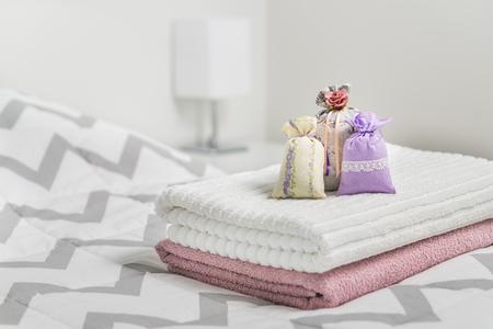 Duftende Beutel auf Handtüchern auf dem Bett Duftende Beutel für gemütliches Zuhause. Getrockneter Lavendel in Dekoration Beutel im Schlafzimmer. Einrichtungszubehör und helle Farbe Skandinavische Innenarchitektur. Aroma potpourri