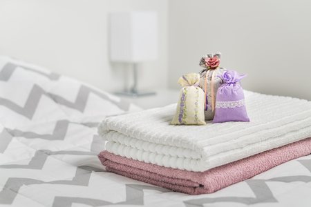 Geparfumeerde zakjes op handdoeken op bed. Geurige zakjes voor een gezellig huis. Gedroogde lavendel in decoratiezakken in slaapkamer. Inrichtingstoebehoren en lichtkleur Scandinavisch interieur. Aroma potpourri. Stockfoto