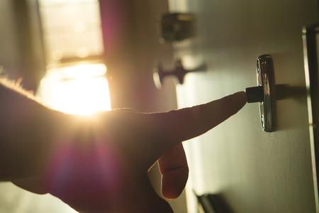 핑거를 눌러 맑은 아파트 건물 복도에서 초인종입니다. 아파트 블록에서 손을 울리는 문 종소리 닫습니다. 창문에서 햇빛과 빛이 새어 나옵니다. 행복