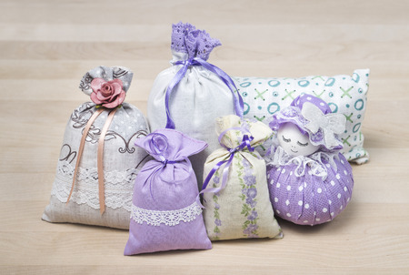 Bunch of different scented sachets for decoration on wooden board. Many fragrant pouches on table. Aromatic potpourri set. Bags filled with lavender. Decorative interior design items on table. Foto de archivo