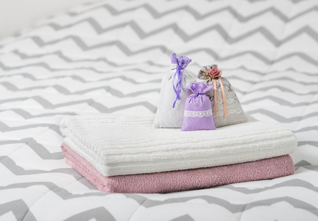 potpourri: Aromatic potpourri set on bed. Three lavender scent pouches on towels. Scented sachets in bedroom. Fragrance bags for fresh home. Decoration, furnishing and storage items.