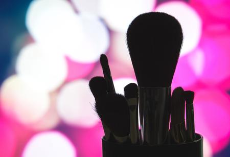 메이크업 브러쉬 핑크 bokeh 배경으로 실루엣을 설정합니다. 흐리게 도시의 불빛에 미용 제품의 개요. 밤 조명에서 어두운 그림자에 화장품 blender입니다. 서비스 또는 자습서 마케팅. 스톡 콘텐츠 - 81102310
