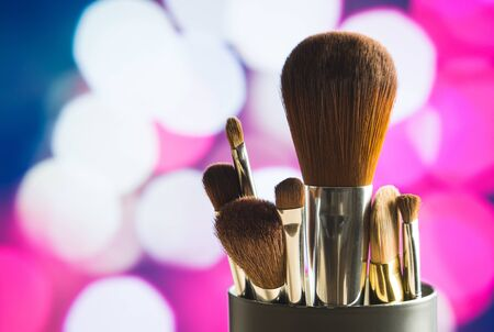 grooming product: Make up concept on pink and purple background. Close up of beauty brushes set on abstract backdrop. Modern and stylish look. Bokeh balls and city lights.