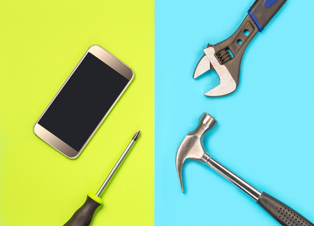 Smartphone repair concept for cellphone fixing companys marketing. Fix broken telephones and solve virus spyware problems. Cellphone and tools on colorful vibrant light green and blue background.