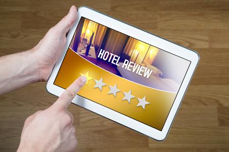 Slechte hotelbeoordeling. Teleurgestelde en ontevreden klant die een vreselijke beoordeling geeft met een tablet op een denkbeeldige kritieksite, applicatie of website. Eén op vijf sterren voor logies of logies. Stockfoto