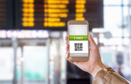 internet terminal: E-ticket on smartphone screen with timetable in the blurred background. Buying online ticket from internet. Universal public transportation terminal. Bus, train, metro, subway or underground station