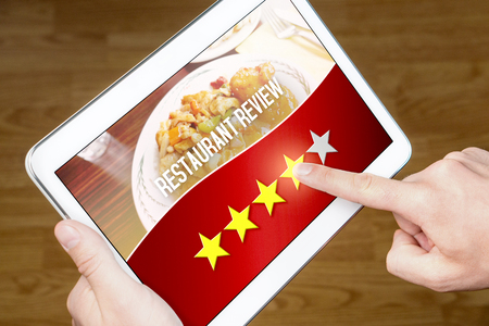 Good restaurant review. Satisfied and happy customer giving great rating with tablet on an imaginary criticism site, application or website. Four out of five stars to tavern, cafe or bistro.
