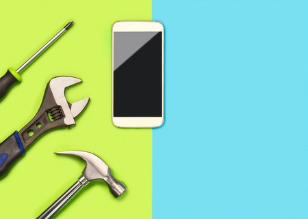 Mobile phone repair background or layout for smartphone fixing company. Banner with a lot of free blank copy space for text and content. Cellphone and tools on fun vibrant light green and blue table Stock Photo