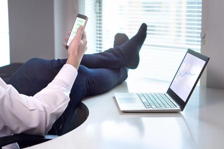 성공적인 사업은 잘 가고 있습니다. 소득 상승 하 고 쉽게 돈을 받고있는 동안 테이블에 발 사무실에 누워 사업가. 주식 시장이 올라갑니다. 사무실에서 스마트 폰 및 노트북 기업가입니다. 스톡 콘텐츠 - 95475106
