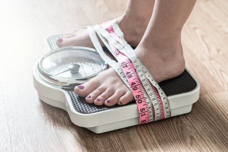 Anorexia and eating disorder concept. Feet tied up with measuring tape to a weight scale. Addiction and obsession to weight loss.