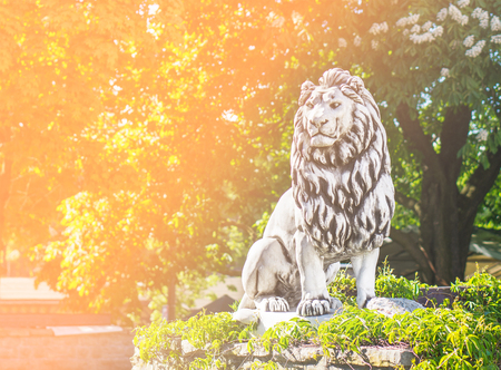 Lion statue standing in forest and nature. Perfect background template for motivation, courage and determination related quote or text. Success concept with orange fade filter and copy space.