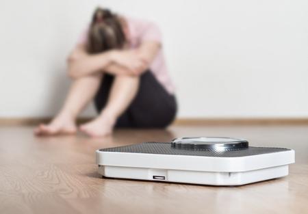 Concept d'échec de perte de poids. Échelle et femme déprimée, frustrée et triste assise sur le sol, tenant la tête et les bras sur les genoux.