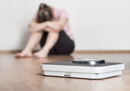 Weight loss fail concept. Scale and depressed, frustrated and sad woman sitting on floor holding head and arms on knees. Stockfoto