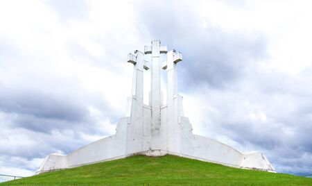 Three Crosses in Vilnius, Lithuania on a hill against stormy and dramatic clouds.