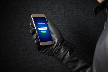 Mobile banking hack and cyber security concept. Hacker and criminal login to persons online bank application and steal money from account with smartphone. Thief with black leather gloves. Stock Photo - 95476159