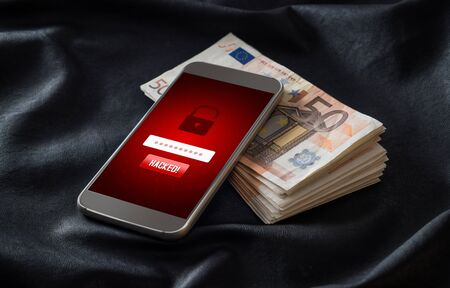 Hacked. Cyber security and mobile hacking concept. Smartphone and stack of money and 50 euro bills. Online criminal login to personal information and data. Imagens