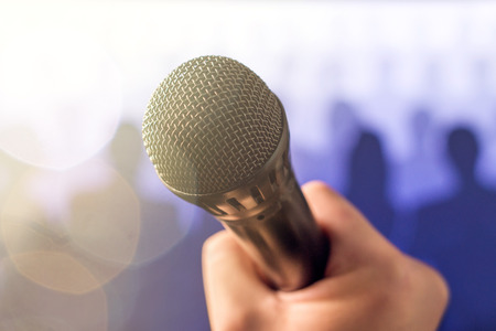 Public speaking and giving speech concept. Hand holding microphone in front of a crowd of silhouette people with lens flare and sun light leak bokeh. Singing to mic in karaoke or talent show concept.
