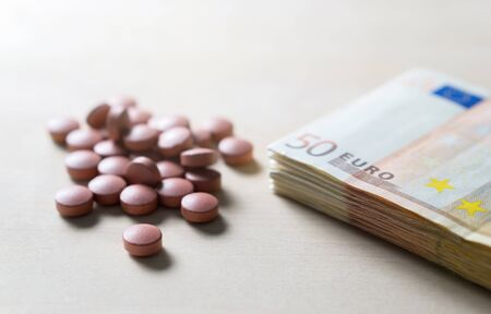 Medical business or prices concept. Making money in pharmaceutical industry or high medical expenses. Also drug dealing, dealer or trade. Pills, medicine, tablets and 50 euro bills and money on table.