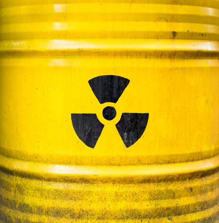 Radioactive sign, icon and symbol on yellow nuclear waste barrel.