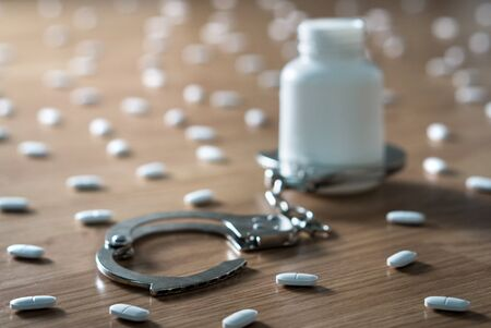 Medicine bottle handcuffed and surrounded by many pills. Drug addiction, medical abuse and narcotics hook and dependence concept. Tablet overdose. Withdrawal symptoms, depression and problem.