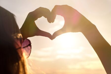 Woman making heart with hands in sunset. Love symbol in sunny summer night. Happy and carefree lifestyle.